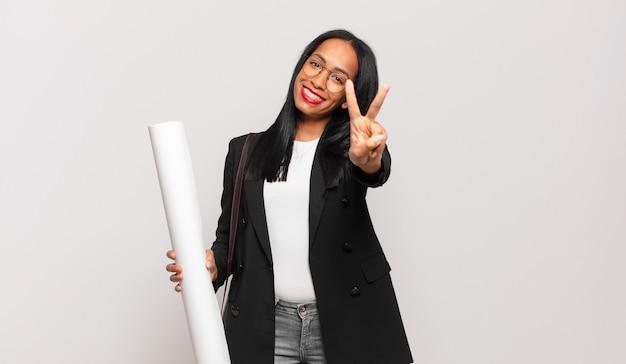 Jeune femme noire souriante et semblant amicale, montrant le numéro deux ou la seconde avec la main en avant, comptant à rebours. concept d'architecte