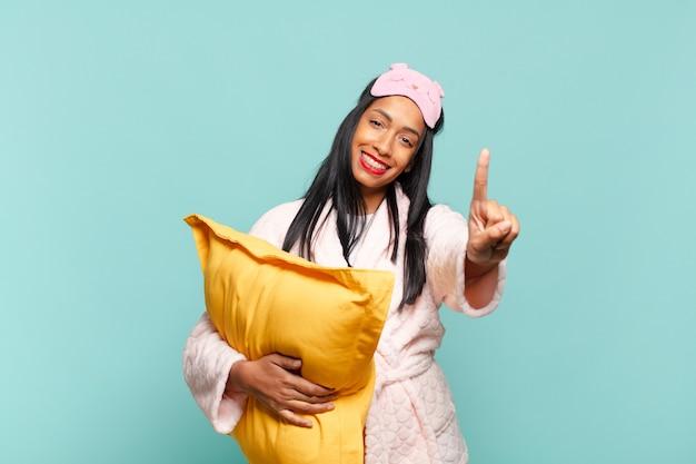 Jeune femme noire souriante et semblant amicale, montrant le numéro un ou le premier avec la main vers l'avant, compte à rebours. concept de pyjama