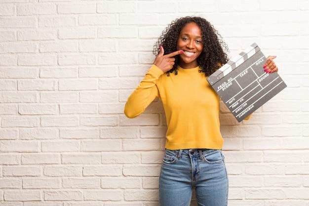 Jeune femme noire sourit, pointe sa bouche, concept de dents parfaites, dents blanches, a une attitude joyeuse et joviale