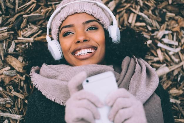 Jeune femme noire sur le téléphone portable se trouvant sur des morceaux de bois près du palais royal de madrid en hiver