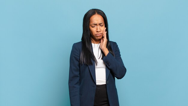 Jeune femme noire tenant la joue et souffrant de maux de dents douloureux, se sentant malade, misérable et malheureux, à la recherche d'un dentiste. concept d'entreprise