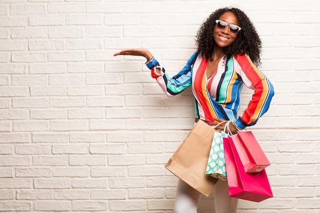 Jeune femme noire tenant quelque chose avec les mains, montrant un produit, souriante et gaie