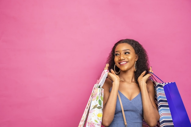 Jeune femme noire tenant des sacs à provisions excité
