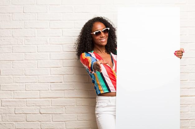 Jeune femme noire tendre la main pour saluer quelqu'un ou faire des gestes pour aider, heureuse et excitée