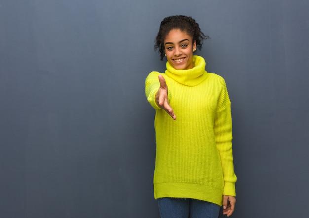 Jeune femme noire tendre la main pour saluer quelqu'un