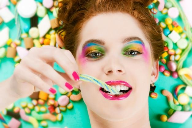 Jeune femme avec de nombreux bonbons ou bonbons malsains, elle a la dent sucrée