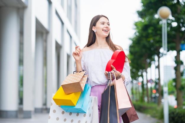 Jeune femme avec de nombreux sacs à provisions