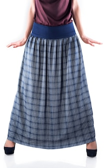 Jeune femme non identifiée dans une jupe longue et talons hauts posant sur fond blanc.