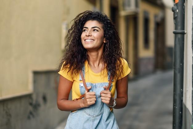Jeune femme nord-africaine avec une coiffure frisée noire à l'extérieur.