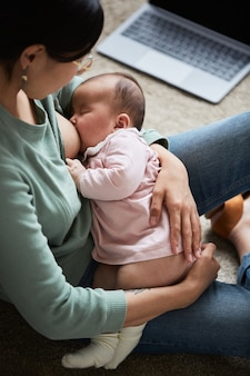 Jeune femme nourrissant son bébé endormi avec du sein assis dans la chambre