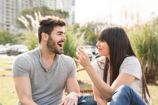 Jeune femme nourrit de fraises à son petit ami dans le parc