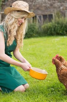 Jeune femme nourrit son poulet