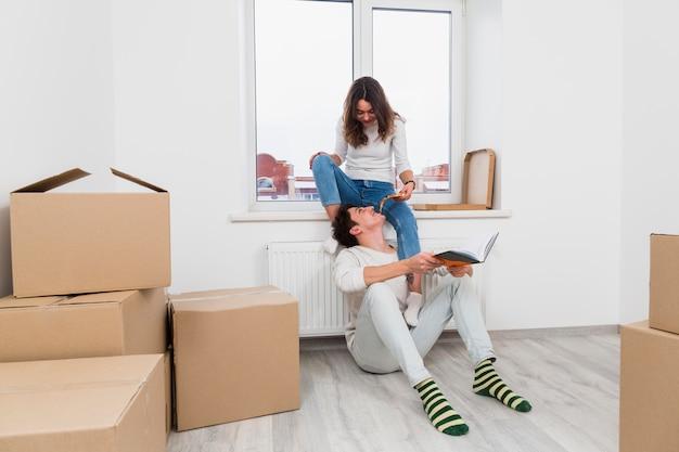 Jeune femme nourrit une tranche de pizza à son petit ami dans leur nouvelle maison