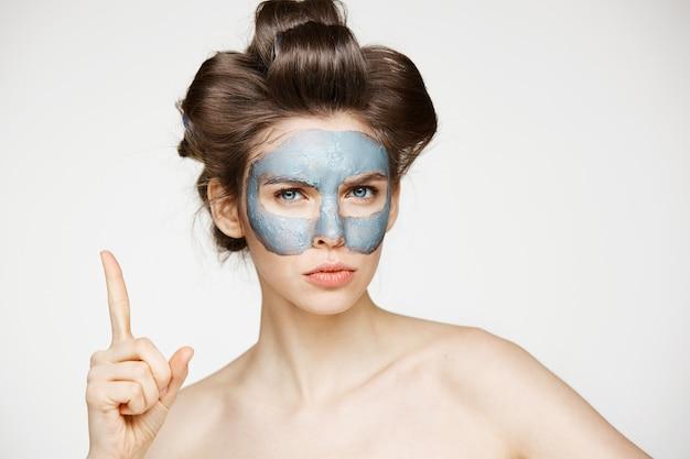 Jeune femme nue en bigoudis et masque facial fronçant les sourcils. soins de beauté et cosmétologie.