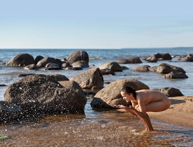 Jeune femme nue debout dans la mer et jouant avec de l'eau