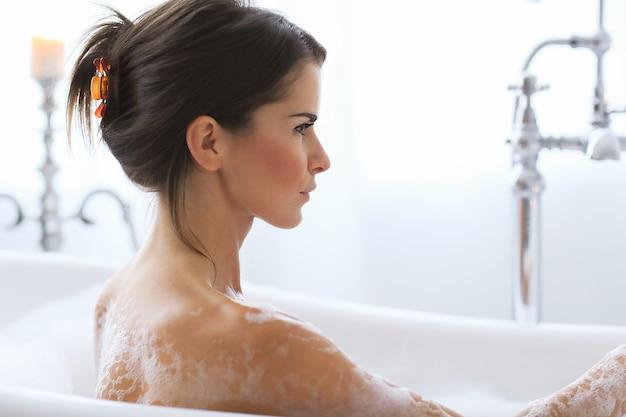 Jeune femme nue prenant un bain mousseux relaxant