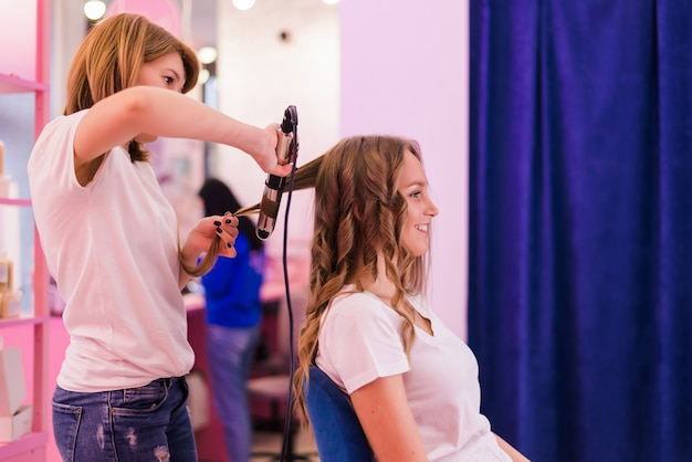 Jeune femme obtenant une coiffure au salon. le coiffeur transforme les cheveux lisses en cheveux bouclés à l'aide d'un fer à friser.
