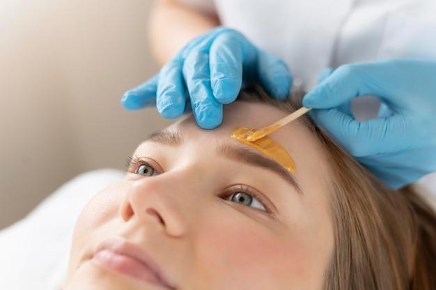 Jeune femme obtenant un traitement des sourcils au salon de beauté