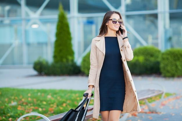Jeune femme occasionnelle va à l'aéroport à la fenêtre avec valise en attente de l'avion