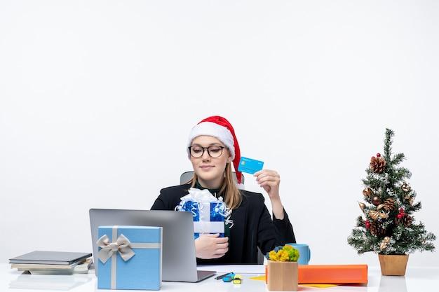 Jeune femme occupée avec chapeau de père noël et portant des lunettes assis à une table tenant un cadeau de noël et une carte bancaire sur fond blanc