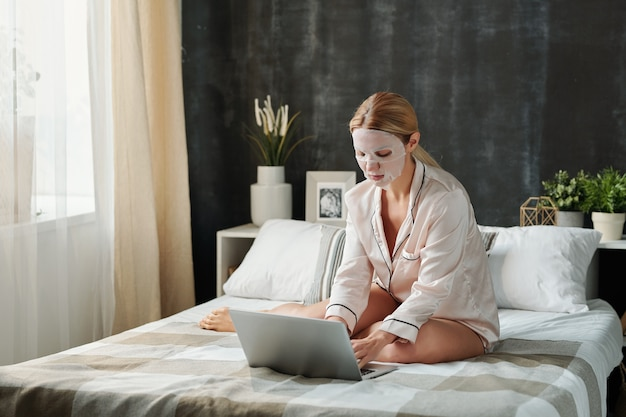 Jeune femme occupée en pyjama ayant un masque textile hydratant sur le visage assis sur le lit et en naviguant sur le net