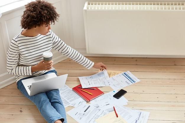 Jeune femme occupée travaillant à la maison