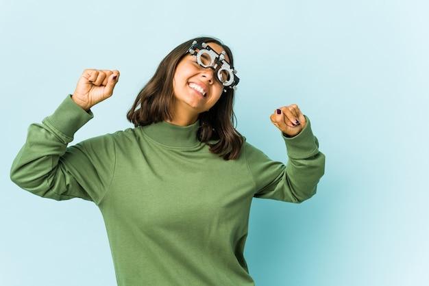 Jeune femme oculiste sur mur isolé célébrant une journée spéciale, saute et lever les bras avec énergie