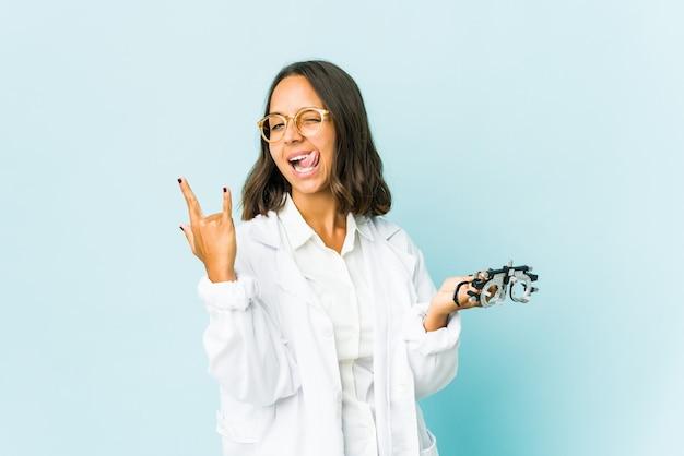 Jeune femme oculiste sur mur isolé montrant le geste de la roche avec les doigts