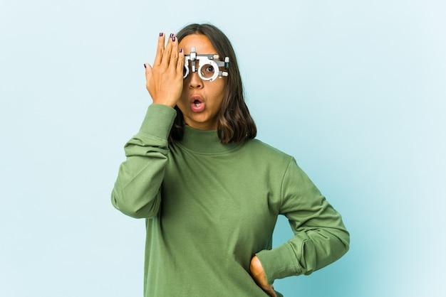 Jeune femme oculiste sur mur isolé s'amusant couvrant la moitié du visage avec palm