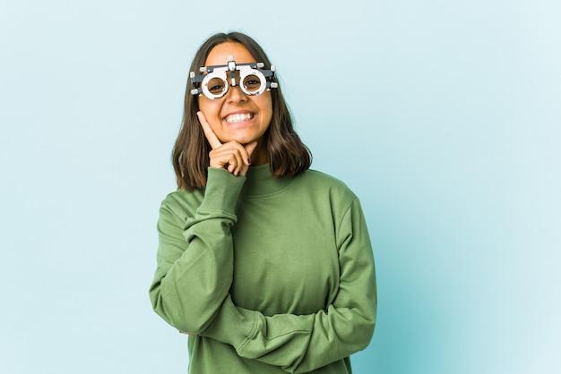 Jeune femme oculiste sur mur isolé souriant heureux et confiant, toucher le menton avec la main