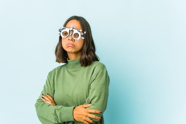 Jeune femme oculiste sur mur isolé suspect, incertain, vous examinant