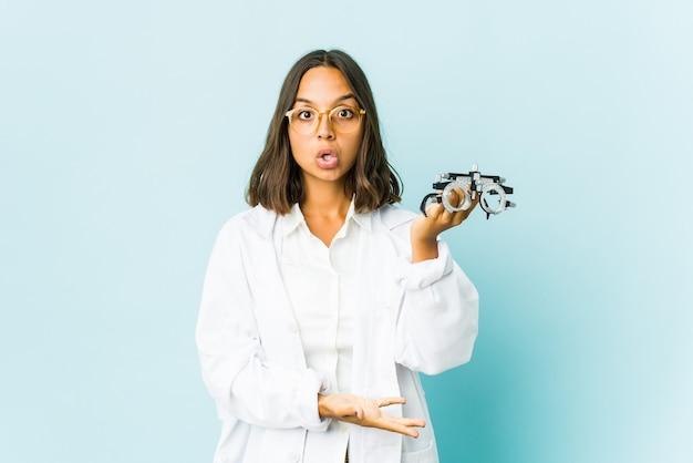 Jeune femme oculiste sur mur isolé tenant quelque chose à deux mains, présentation du produit