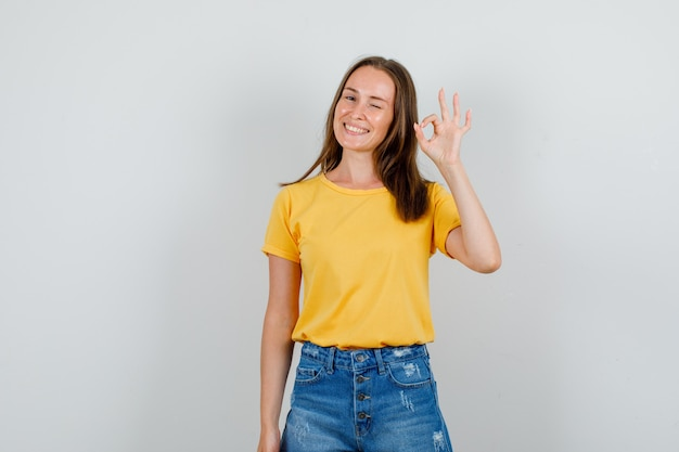 Jeune femme oeil clignotant avec signe ok en t-shirt, short et à la joyeuse