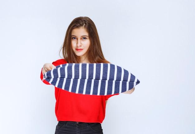 Jeune femme offrant un oreiller rayé bleu au client.