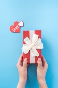 Une jeune femme offre un cadeau avec une étiquette en forme de coeur et un texte d'amour. concept de la saint-valentin