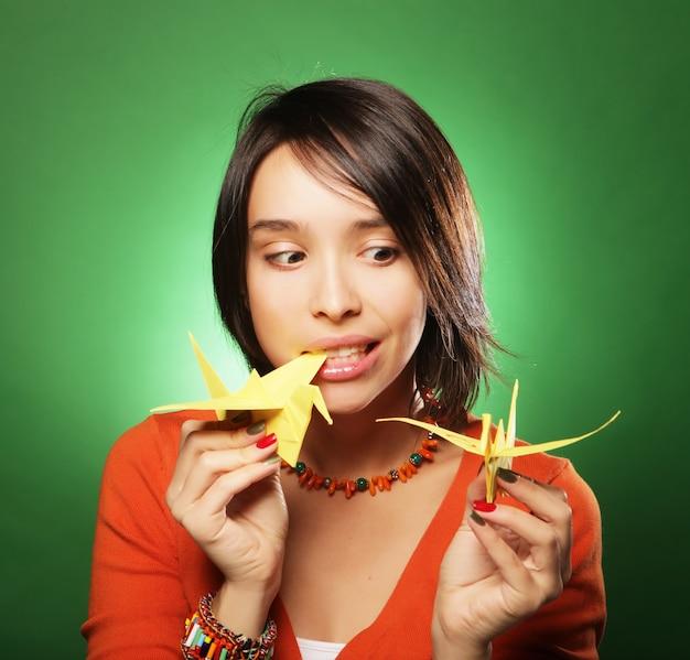 Jeune femme avec oiseau en papier sur fond vert
