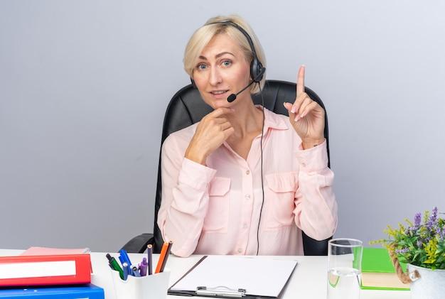 Jeune femme opératrice de centre d'appels impressionnée portant un casque assis à table avec des outils de bureau pointant vers le haut