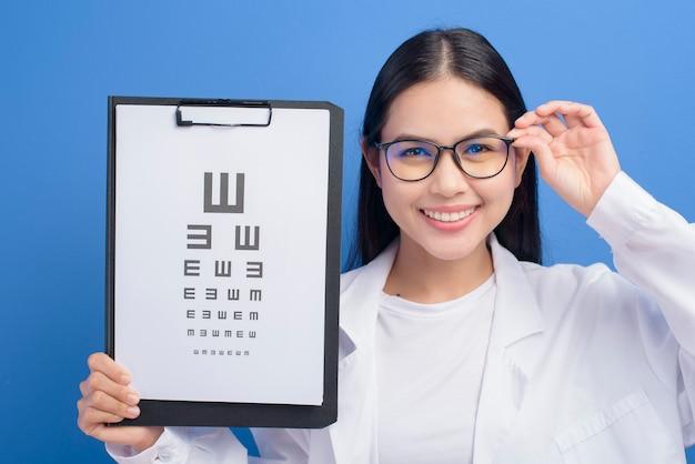 Une jeune femme ophtalmologiste avec des lunettes tenant un tableau des yeux sur bleu, concept de soins de santé