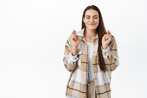 Une jeune femme optimiste ferme les yeux et attend les résultats, croise les doigts pour la chance et les sourires, anticipe les bonnes nouvelles, prie, mendie pour un résultat positif, mur blanc