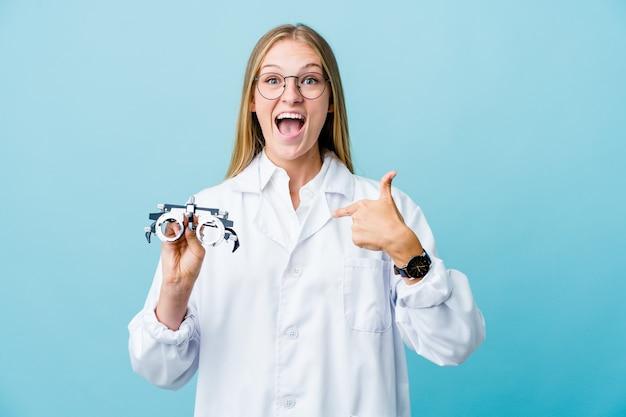 Jeune femme optométriste russe sur bleu surpris pointant avec le doigt, souriant largement.