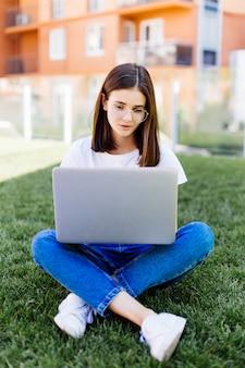 Jeune femme avec ordinateur portable assis sur l'herbe verte et à la recherche d'un affichage à l'extérieur