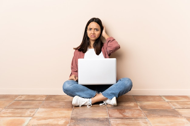 Jeune femme avec un ordinateur portable assis sur le sol ayant des doutes
