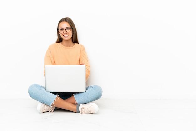 Jeune femme avec un ordinateur portable assis sur le sol en gardant les bras croisés en position frontale