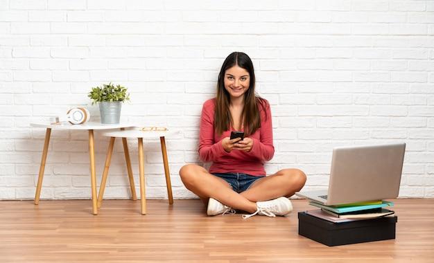 Jeune femme avec un ordinateur portable assis sur le sol à l'intérieur en envoyant un message avec le mobile
