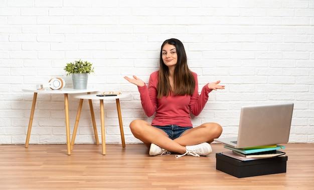 Jeune femme avec un ordinateur portable assis sur le sol à l'intérieur faisant le geste de doutes