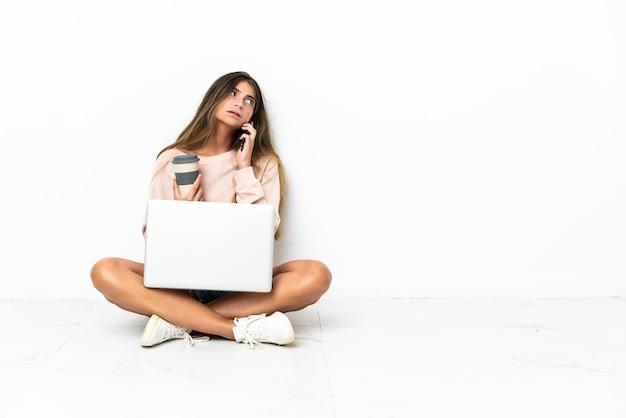 Jeune femme avec un ordinateur portable assis sur le sol isolé sur fond blanc tenant du café à emporter et un mobile