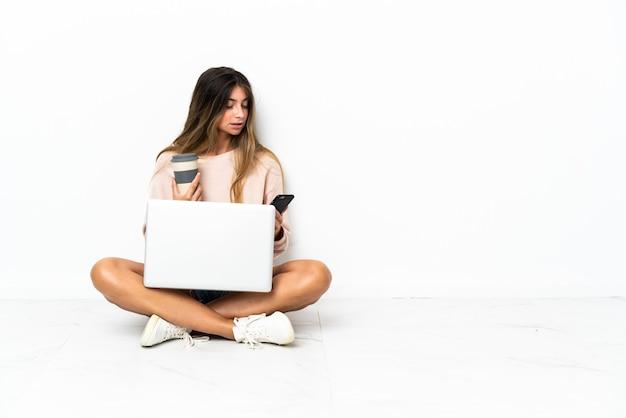 Jeune femme avec un ordinateur portable assis sur le sol isolé