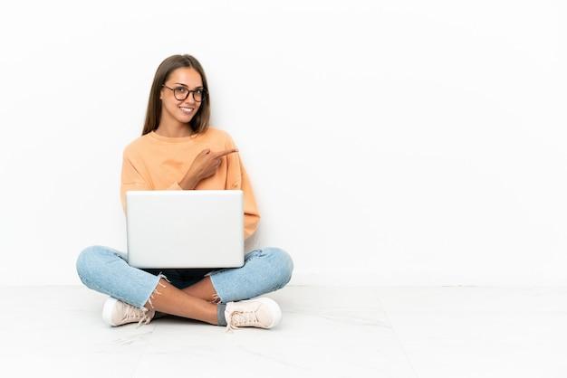 Jeune femme avec un ordinateur portable assis sur le sol pointant le doigt sur le côté