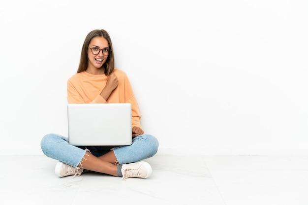 Jeune femme avec un ordinateur portable assis sur le sol pour célébrer une victoire