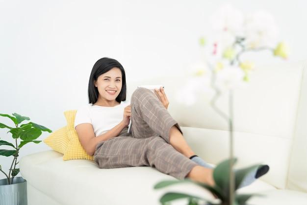Jeune femme avec un ordinateur portable moderne assis sur un canapé à la maison